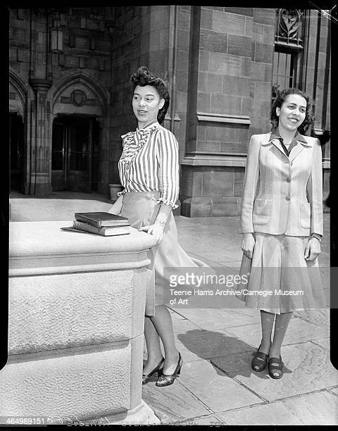 Louise W Johnson wearing wrap skirt blowing in wind standing behind stone ledge with another woman on right in front of Cathedral of Learning...