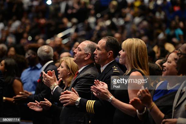 Louisiana Gov John Bel Edwards second left and Baton Rouge Police Chief Carl Dabadie Jr second right applaud during the funeral of Baton Rouge police...