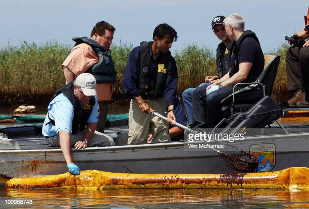 Louisiana Governor Bobby Jindal scoops crude oil from the water during a tour of areas where oil has come ashore with Plaquemines Parish President...
