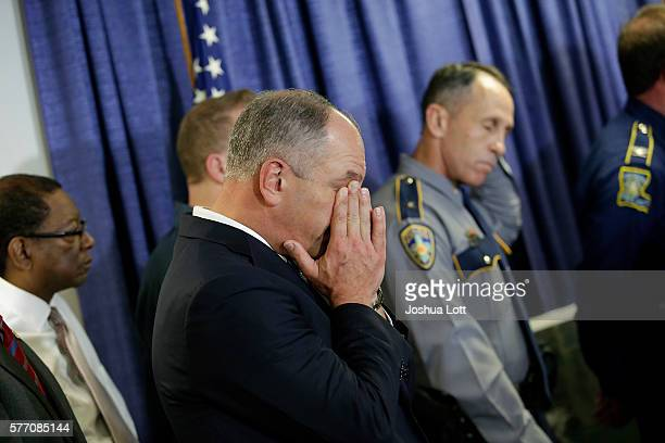 Louisiana Governor John Bel Edwards center wipes away tears after speaking about three local police officers who were killed by gunman Gavin Long...