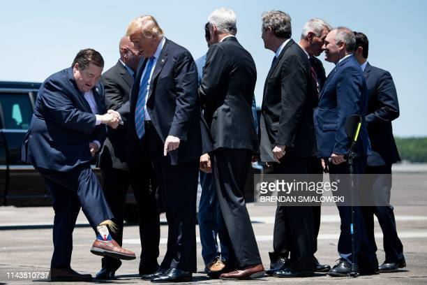 TOPSHOT Louisiana Lt Governor Billy Nungesser shows US President Donald Trump his socks after the President arrives at Chennault International...