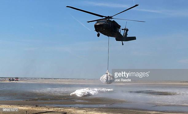 Louisiana National Guard helicopter airlifts sling load sand bags into place as they create a barrier in an attempt to protect an estuary from the...