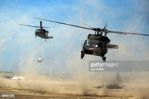 Louisiana National Guard helicopters airlift sling load sand bags into place as they create a barrier in an attempt to protect an estuary from the...
