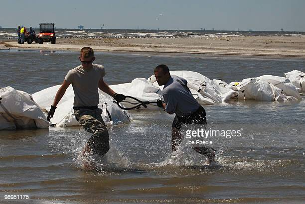 Louisiana National Guard members retrieve a sling load cable as helicopters drop sand bags into place as they create a barrier in an attempt to...