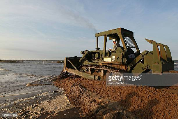 Louisiana National Guard Sergeant George Achee uses a bulldozer to create a earthen barrier as they try to protect an estuary from the massive oil...