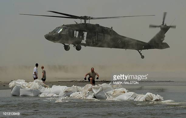 """Louisiana National Guardsmen use Blackhawk helicopters build a dam to protect the fragile wetlands known locally as """"Bayou"""" near the town of Grand..."""