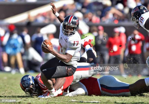 Louisiana Ragin' Cajuns quarterback Levi Lewis tries to keep his balance while his feet are wrapped up by a Mississippi Rebels defender during the...