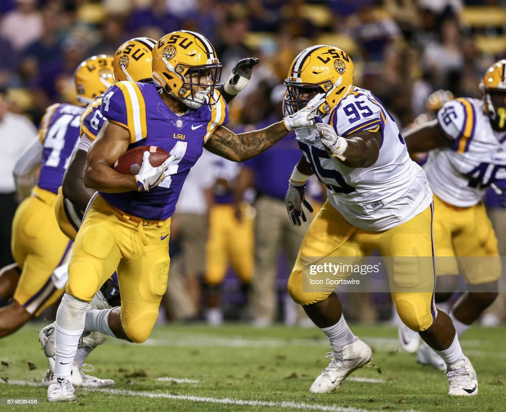 Louisiana State Tigers quarterback Lindsey Scott Jr. (14) is forced out the pocket by defensive tackle Edwin Alexander (95) during the annual Louisiana State Tigers purple-gold spring game at Tiger Stadium on April 22, 2017 at Tiger Stadium in Baton Rouge, LA. Purple team won 7-3.