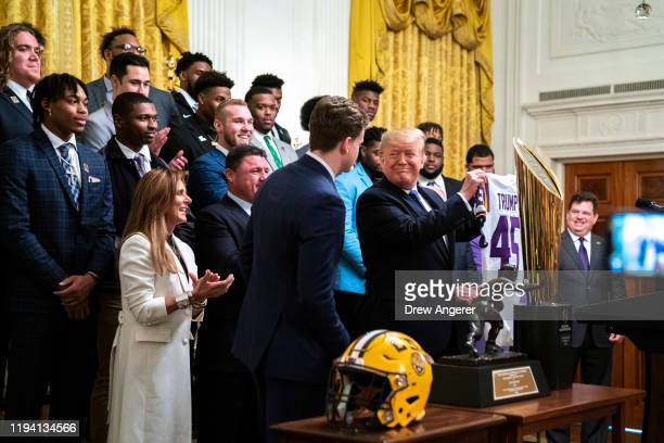 Louisiana State University quarterback Joe Burrow presents President Donald Trump with a jersey during an event to honor this year's NCAA football...