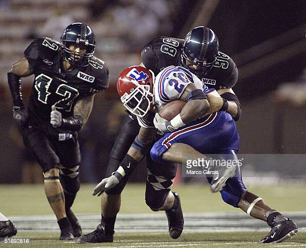 Louisiana Tech's running back Ryan Moats runs into Hawaii's defensive lineman Melila Purcell with defensive back Leonard Peters close behind during...