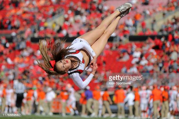 Louisville Cardinals cheerleader does a flip in the end zone to celebrate a Louisville touchdown during the fourth quarter of the college football...