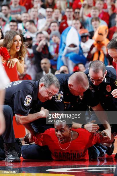 Louisville Cardinals fan is subdued by police after running onto the floor in the first half of the game against the Miami Hurricanes at KFC YUM...