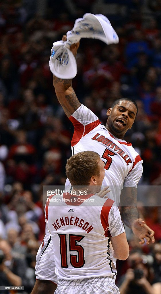 Louisville Cardinals forward Chane Behanan, wearing injured teammate Kevin Ware's jersey, leaps into the air with teammate Tim Henderson (15) at the end of their game against Duke in the NCAA Tournament at Lucas Oil Stadium in Indianapolis, Indiana, Sunday, March 31, 2013. Louisville defeated Duke, 85-63.