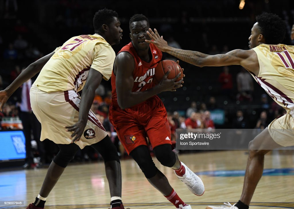 Louisville Cardinals forward Deng Adel (22) drives to the basket around Florida State Seminoles center Christ Koumadje (21) during the ACC men's tournament game between the Louisville Cardinals and the Florida State Seminoles on March 7, 2018, at Barclays Center in Brooklyn, NY.