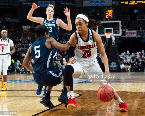 Louisville Cardinals Guard Asia Durr dribbles the ball and gets a blocking foul on Connecticut Huskies Guard Crystal Dangerfield defending during the...