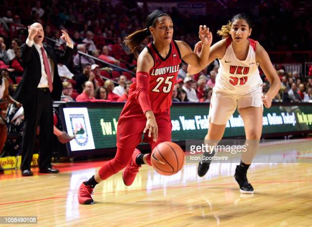 Louisville Cardinals guard Asia Durr drives past Western Kentucky Lady Toppers guard Meral Abdelgawad during a college basketball game between the...