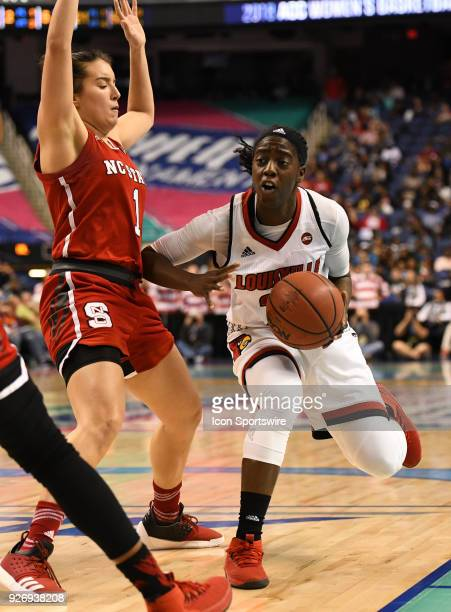 Louisville Cardinals guard Jazmine Jones drives on North Carolina State Wolfpack guard Aislinn Konig during the ACC women's tournament game between...