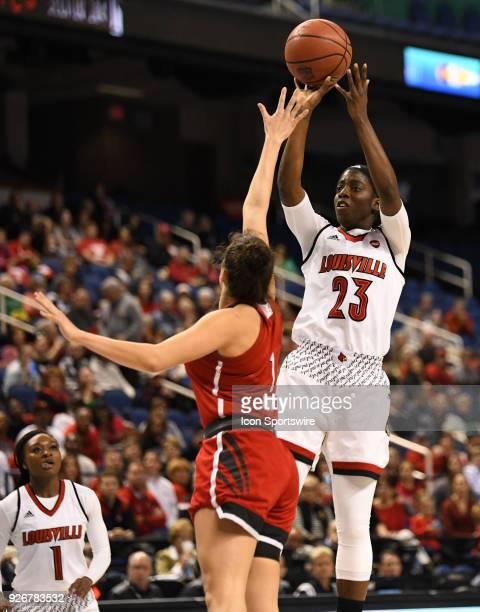 Louisville Cardinals guard Jazmine Jones shoots over North Carolina State Wolfpack guard Aislinn Konig during the ACC women's tournament game between...