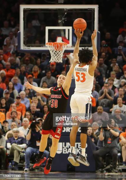 Louisville Cardinals guard Ryan McMahon attempts to block Virginia Cavaliers guard Tomas Woldetensae jump shot during a game between the Louisville...