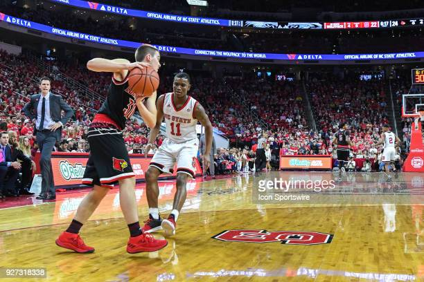 Louisville Cardinals guard Ryan McMahon is defended by North Carolina State Wolfpack guard Markell Johnson as Louisville Cardinals head coach David...