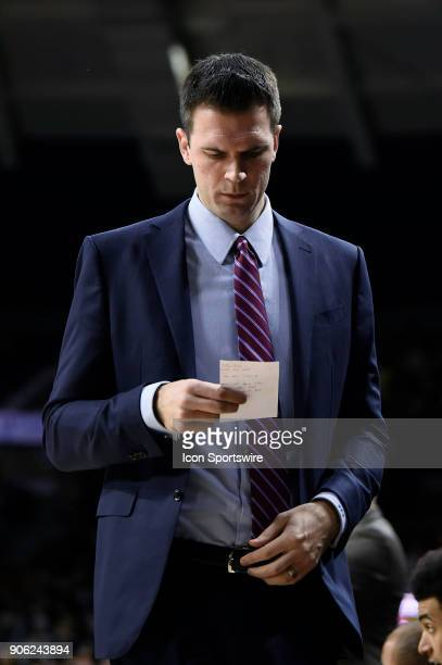 Louisville Cardinals interim head coach David Padgett reviews his notes after a play during the college basketball game between the Louisville...