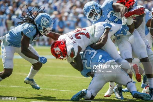 Louisville Cardinals running back Malik Williams is tackled by North Carolina Tar Heels linebacker Cayson Collins defensive end Allen Cater and...