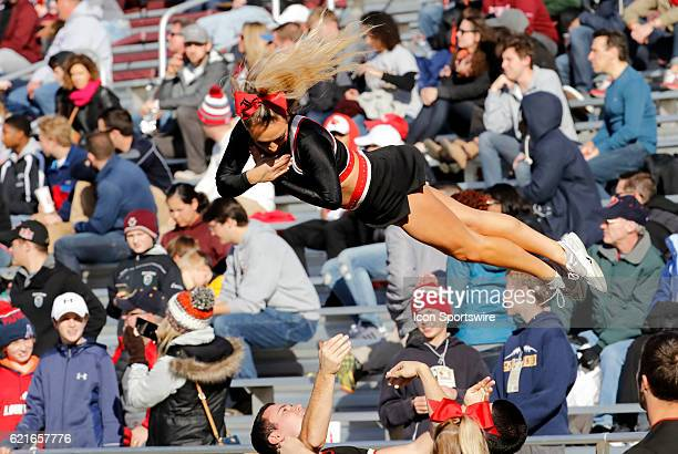 Louisville cheerleader floats back to the waiting arms of her teammates during an ACC Division 1 NCAA football game between the Louisville Cardinals...