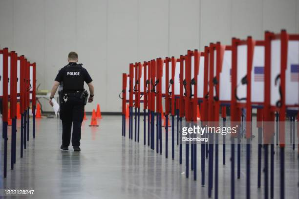 Louisville Metro Police Department officer carries a ballot while voting at a polling location in Louisville, Kentucky, U.S., on Tuesday, June 23,...