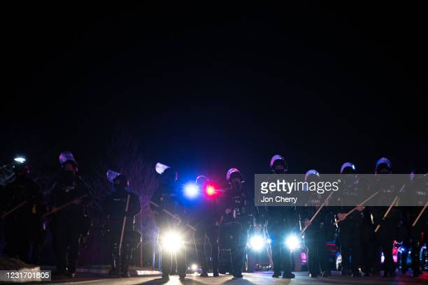Louisville Metro Police Department officers march toward a group of protesters after the Breonna Taylor memorial events on March 13, 2021 in...