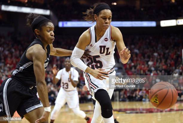 Louisville's Asia Durr and Connecticut's Crystal Dangerfield left pursue the ball at KFC Yum Center in Louisville Ky on Thursday Jan 31 2019...