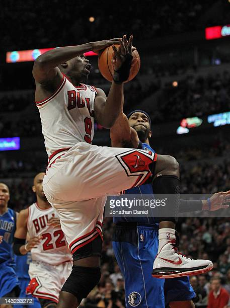 Loul Deng of the Chicago Bulls is fouled while shooting by Vince Carter of the Dallas Mavericks at the United Center on April 21 2012 in Chicago...