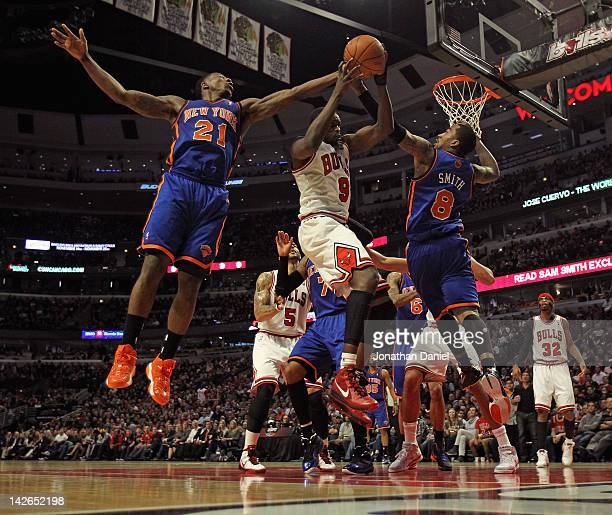 Loul Deng of the Chicago Bulls rebounds between Iman Shumpert and JR Smith of the New York Knicks at the United Center on April 10 2012 in Chicago...