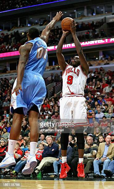 Loul Deng of the Chicago Bulls shoots against Darrell Arthur of the Denver Nuggets during a preseason game at the United Center on October 25 2013 in...