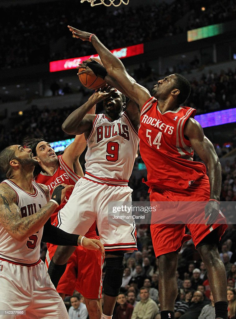 Loul Deng #9 of the Chicago Bulls tries to get off a shot over teammate Carlos Boozer as Luis Scola #4 and Patrick Patterson #54 of the Houston Rockets defend at the United Center on April 2, 2012 in Chicago, Illinois. The Rockets defeated the Bulls 99-93.