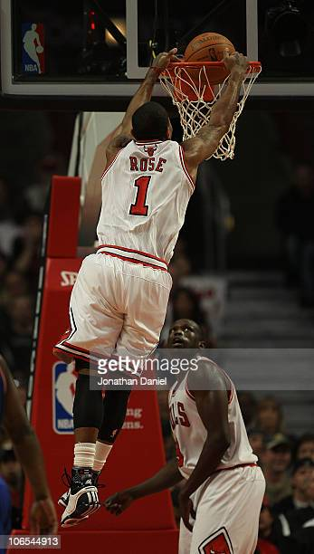 Loul Deng of the Chicago Bulls watches as his teammate Derrick Rose dunks the ball against the New York Knicks at the United Center on November 4...