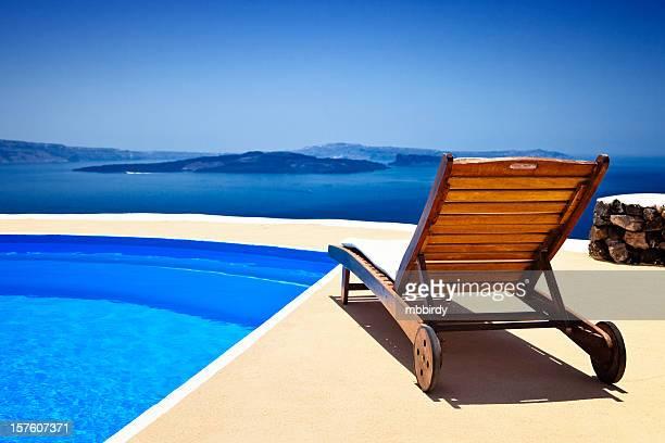 Lounge chair and pool over Santorini caldera