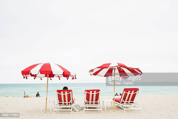 Lounge Chairs And Parasols At Sea Shore Against Clear Sky