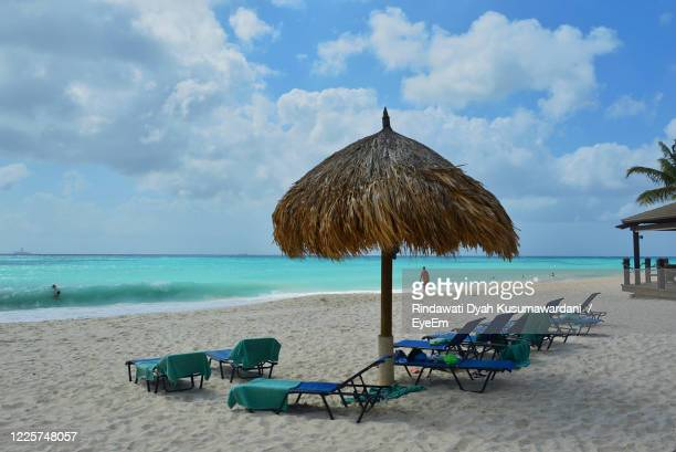 lounge chairs and parasols on beach against sky - oranjestad stockfoto's en -beelden