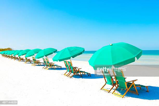 lounge chairs and umbrella at the beach - gulf coast states stock pictures, royalty-free photos & images
