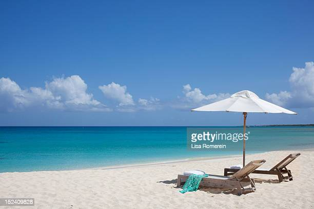 lounge chairs and umbrella on white sand beach - turks and caicos islands stock pictures, royalty-free photos & images