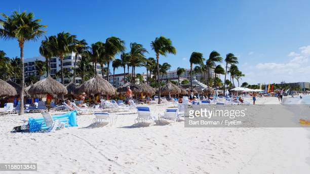 lounge chairs at beach against sky during sunny day in city - aruba stockfoto's en -beelden