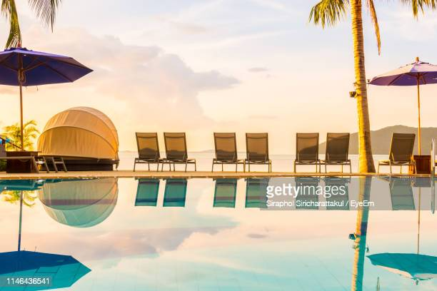 lounge chairs at beach against sky during sunset - sun lounger stock pictures, royalty-free photos & images