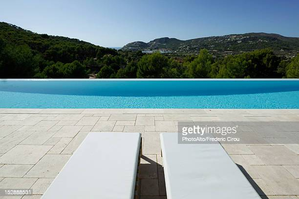 lounge chairs beside swimming pool - poolside stock pictures, royalty-free photos & images