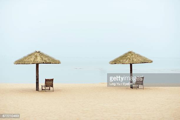 Lounge Chairs By Thatched Roofs On Sandy Beach