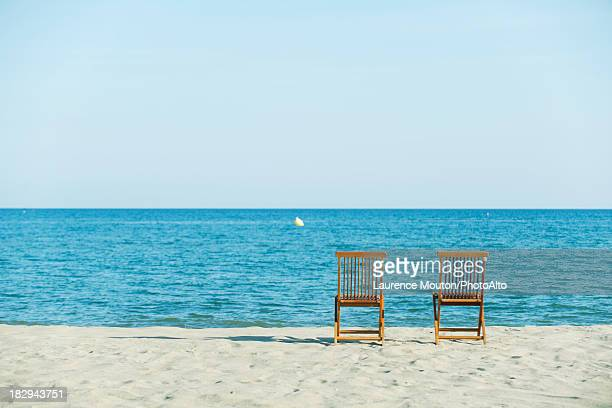 Lounge chairs on beach, rear view