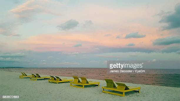 Lounge Chairs On Sea Shore Against Sky During Sunset