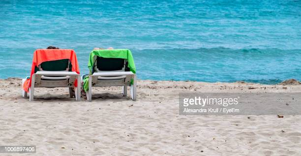 Lounge Chairs On Shore At Beach