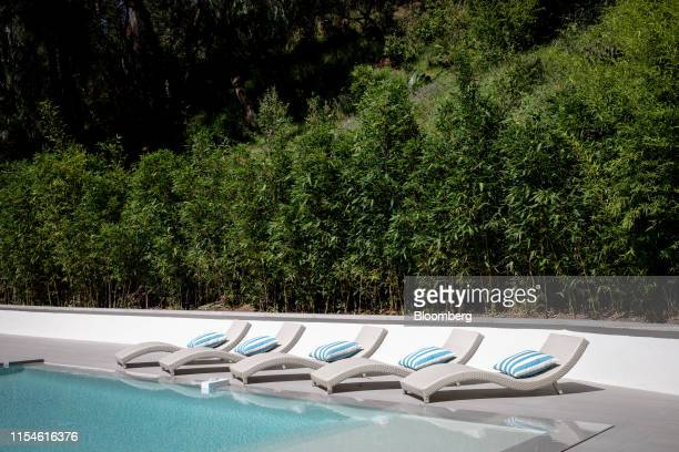 Lounge chairs sit next to the pool outside of a house for sale at 1049 Loma Vista Drive in the Trousdale neighborhood of Beverly Hills, California,...