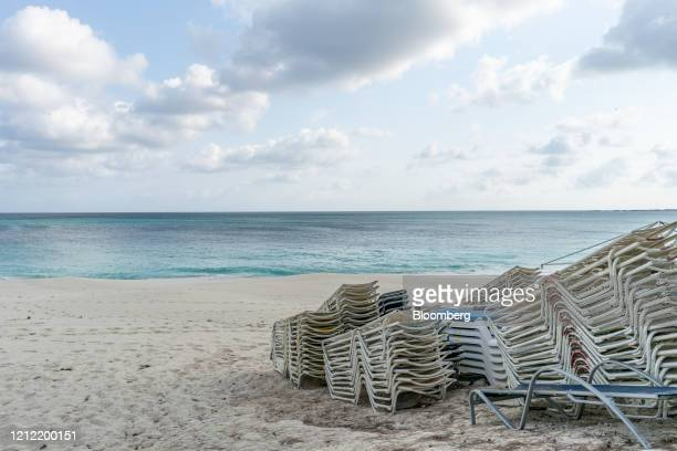 Lounge chairs sit stacked on a beach while temporarily closed in Nassau Bahamas on Friday April 24 2020 The Caribbean countries of Barbados Belize...