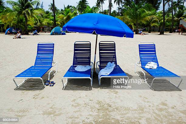 Lounge chairs under a beach umbrella on the beach, Luquillo Beach, Puerto Rico